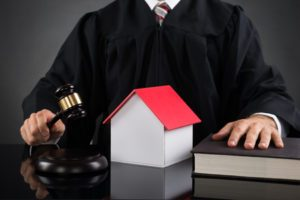 45165781 - close-up of judge holding gavel with house model at desk
